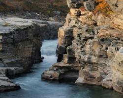Fotografia zachytáva miesto, kde čistá rieka Abeskoaetnu zužuje koryto do kaňonu v národnom parku Abisko. Asi po kilometri zúženín sa vlieva do jazera Tometrask.