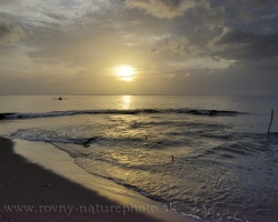 Pokojná hladina Karibského mora odráža posledné lúče slnka, rybári sa vracajú na pláž.