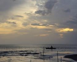 Domorodý rybár čaká v ubúdajúcom svetle na svoj úlovok.