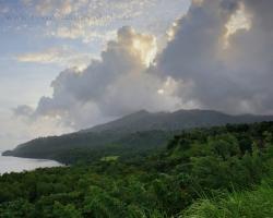 """Prvé ráno - prvý pohľad na """"čierny"""" tajomný ostrov. Kontúry pobrežia a sopky La Soufriere sa kúpu v rannom tropickom opare pod oponou oblakov."""