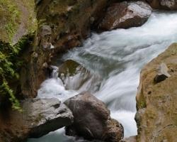 Prudko a zbesilo sa valí voda pod kotlom Trinity vodopádu. Vodopády sú po zosuve svahov v okolí vodopádov oficiálne uzavreté. Po zarastenej cestičke tropickou dźungľou bolo potrebné pre tieto snímky vyzuť topánky šplhať a zatínať nechty po štyroch do mazľavých vyvretých hornín.