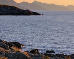Fotografia zachytáva skoré ráno a pobrežie na Lofotoch. Do diaľky sa tiahnu horské chrbty zvažujúce sa do vôd Atlantiku.