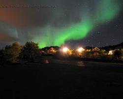 Tento obrázok je fotený smerom od fjordu ponad osadu. Červenkavé svetlo lámp dopľňa zelenú pohyblivú polárnu žiaru. Obrazce na oblohe sa úžasne menia a asi nevytvoria dva rovnaké pohľady.Pocity z tohto divadla sú úžasné.