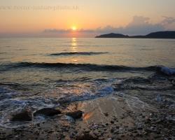 Pohrávajú sa vlnky pokojného mora s ľahkými rannými slnečnými lúčmi.