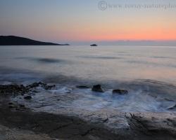 Ranné slnko preniká priehľadnými vodami mora pri pobreží Korziky a sfarbuje krajinu ružovými nádejami krásneho dňa.