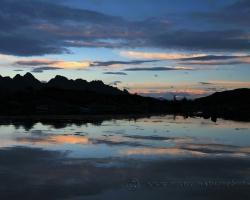 Tak ako postupne miznú slnečné lúče a v posledných dotykoch sfarbujú do oranžova nízke mraky, tmavnú vody fjordu cez modrú do sýto atramentovej.