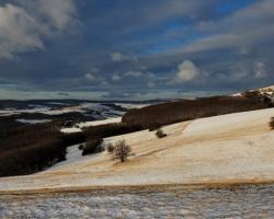 Duje holými bielokarpatskými kopcami nezbedný vietor. Češe a bielou prikrývkou prikrýva zlaté trávy.