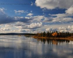 Hra oblakov tieňov vody a farieb veľkej rieky v prírodnej rezervácii Kaitum Fjällurskog vo Švédsku.