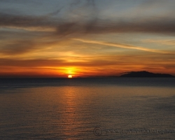 Slnko mizne za morom, všetko sa lúči s farebnými energiami dňa.